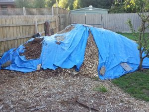 Tarpaulin covering the mulch piles is decaying
